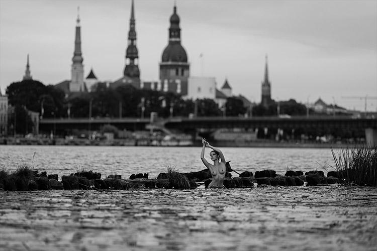 pelde Daugavā ar Rīgas panorāmu fonā