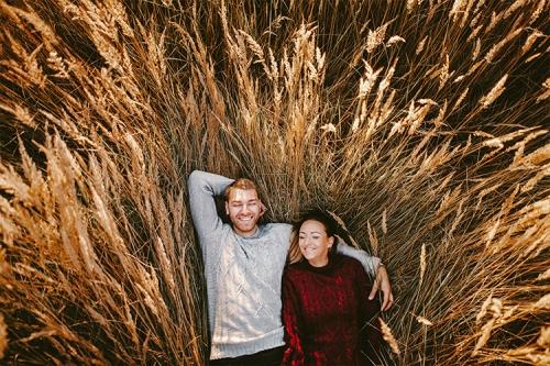 priecīgs pāris apgūlies pļavā