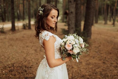 līgava mežā ar rožu pušķi