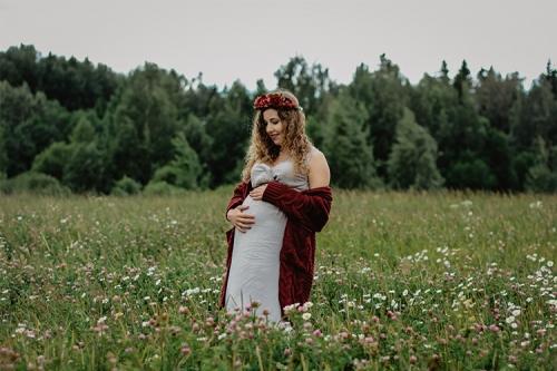grūtniece ziedošā pļavā