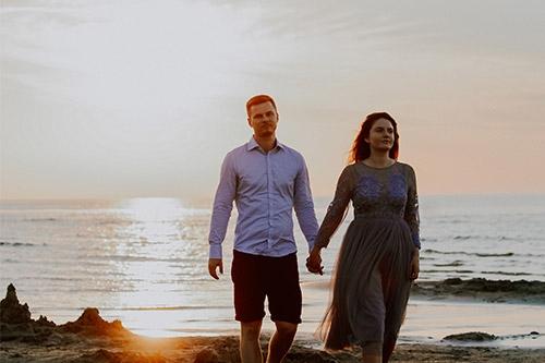 pastaigā saulrietā jūras krastā