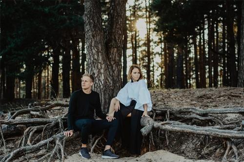 pāris sēž uz koka saknēm