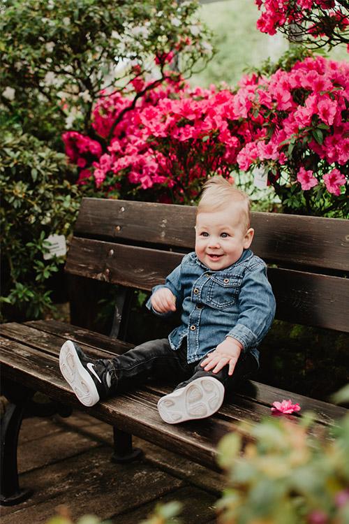 jautrs bērniņš pie ziedošiem krūmiem