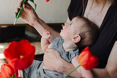 mazulis izbrīnīts skatās uz sarkanu tulpi