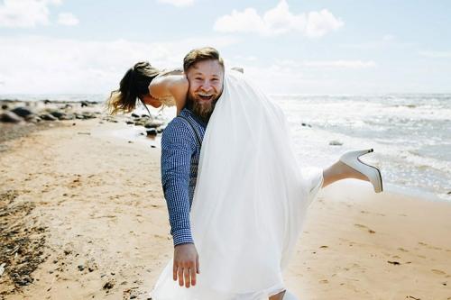 priecīgs vīrs nes sievu uz pleca