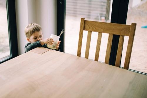 puika virtuvē ar burciņu rokās