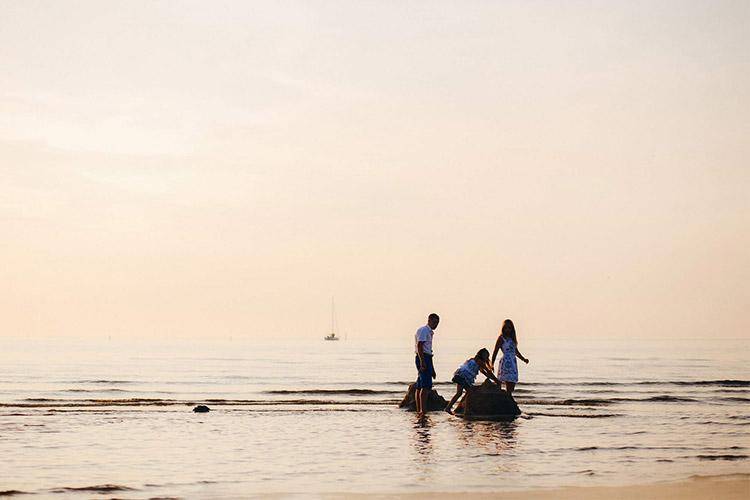 vecāki ar meitu atpūšas pie jūras
