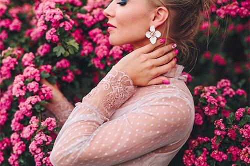 meietene kleitā pie krūma ar rozā ziediem