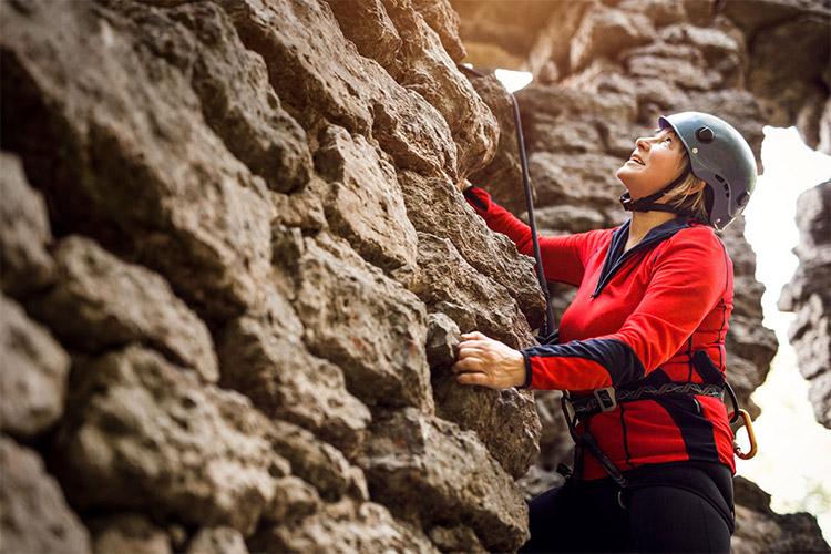 alpīniste pie akmeņainas sienas