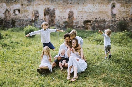 vecāki ar piecām atvasēm pie pilsdrupām