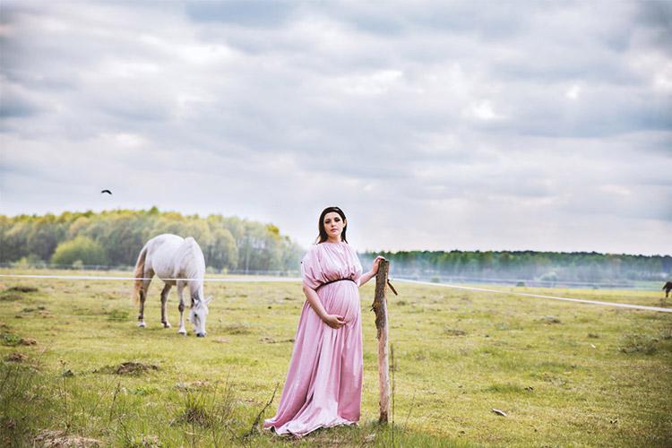 grūtniece rozā kleitā ar baltu zirgu fonā