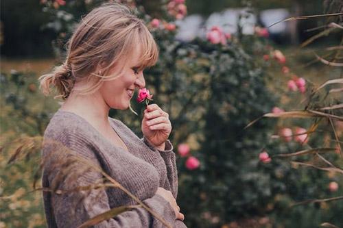 priecīga sieviete pie rozā rožu krūma