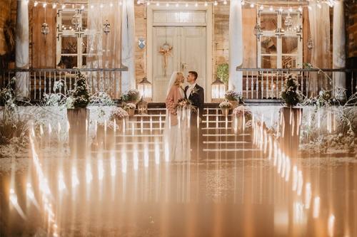 kāzu fotogrāfija izgaismotā mājas priekšā