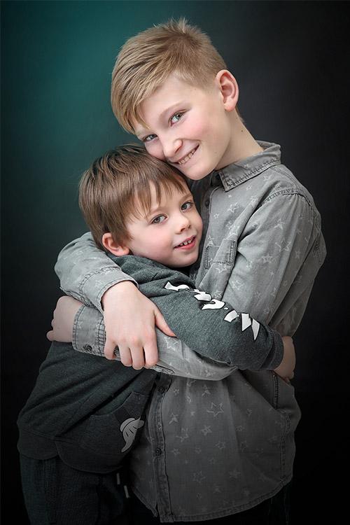 divi draudzīgi puikas fotogrāfējas studijā