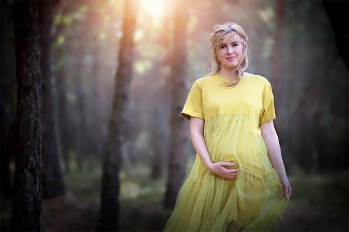 grūtniece dzeltenā kleitā