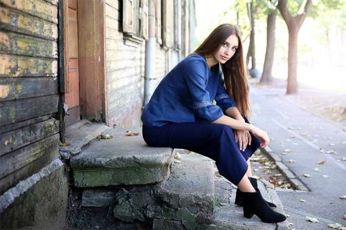 meitene pie senas koka ēkas