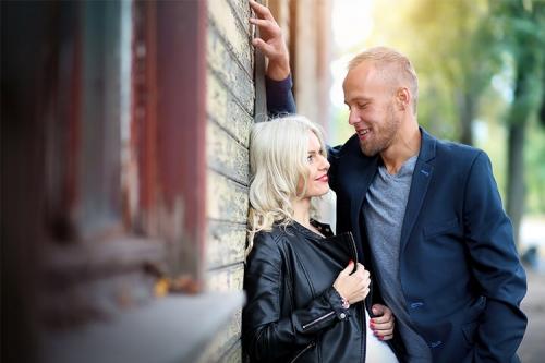 sieviete ar vīrieti pie koka ēkas