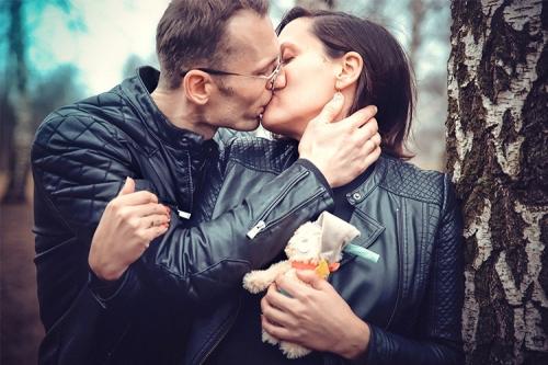 sieviete ar vīrieti ādas jakās skūpstās pie bērza