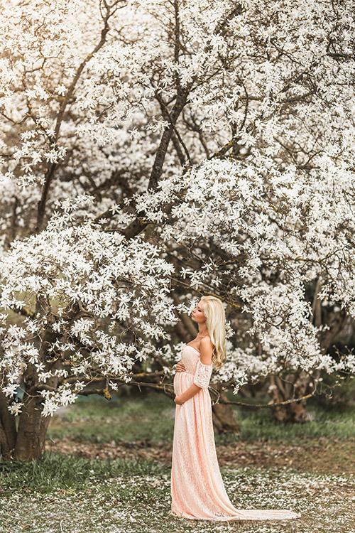 sieviete gaidībās pie ziedoša koka