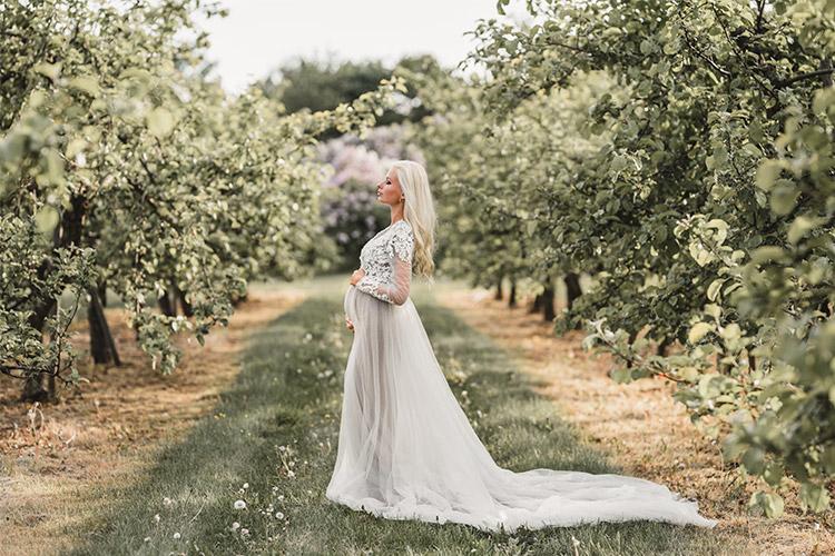 grūtniece garā kleitā ābeļu dārzā