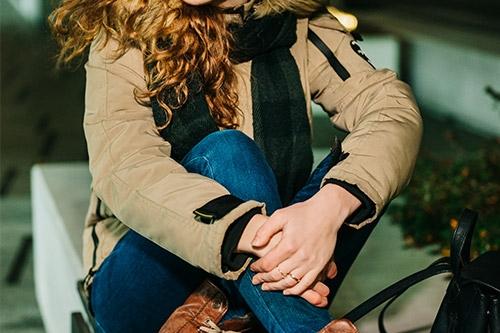 meitene brūnā jakā un zābakos uz soliņa