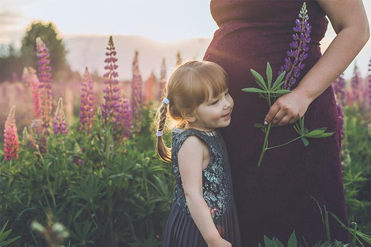 meitenīte ar mammu lupīnu laukā