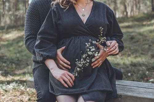 grūtniece ar ziedošu zariņu rokā