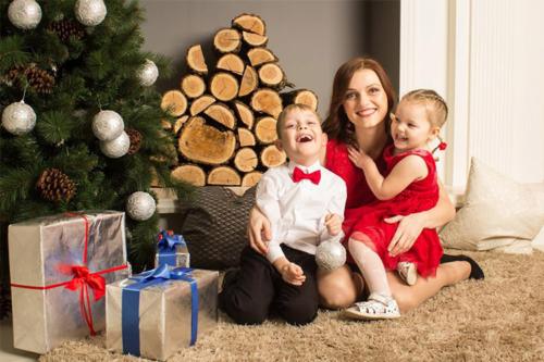 māmiņa ar bērniem pie Ziemassvētku eglītes