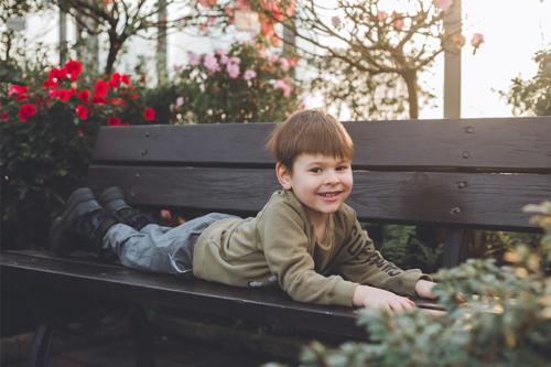 smaidīgs puika uz soliņa parkā