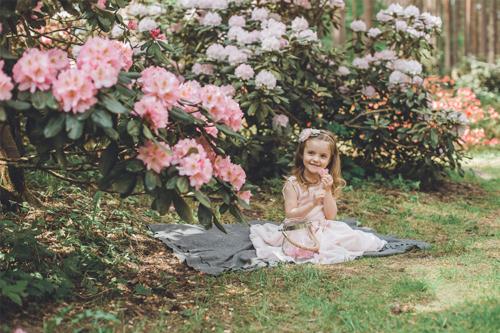 meitenīte pie ziedošiem rododendriem