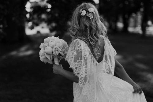 līgava ar lokainiem matiem un baltu puķu pušķi