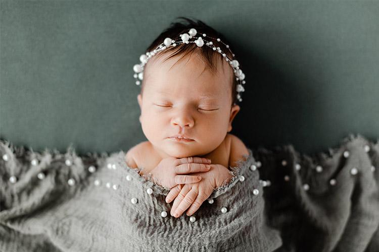 dusošs mazulis ar pērļu rotu