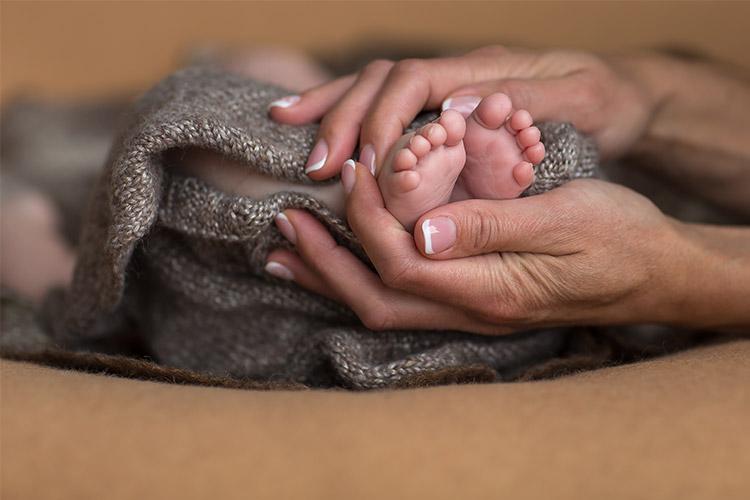 māmiņas rokas ar bērniņa pēdiņām