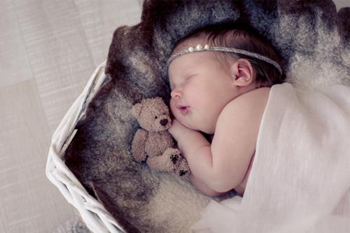 guļoša meitenīte ar brūnu lācīti