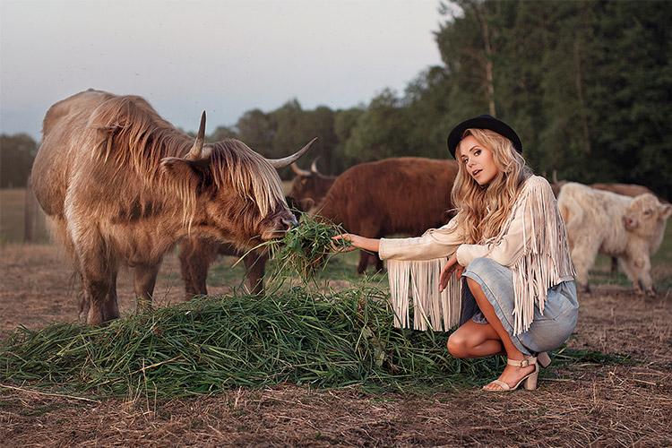 oriģināla fotogrāfija, kurā sieviete atrodas līdzās govij