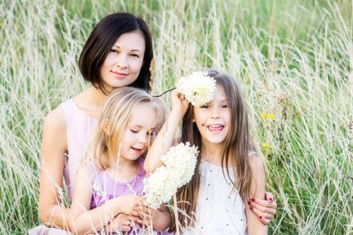 māte ar divām meitām pļavā vicinās ar ziediem