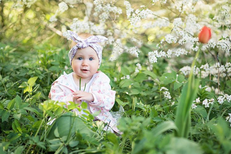 izbrīnīts mazulis zem ziedoša krūma