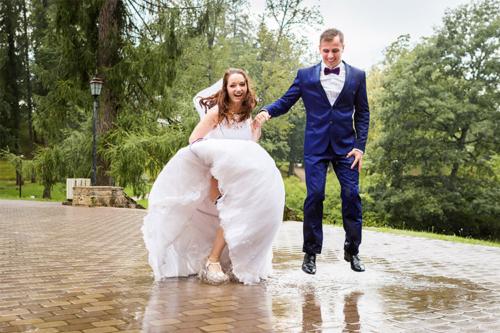 vīrs ar sievu lēkā pa peļķēm