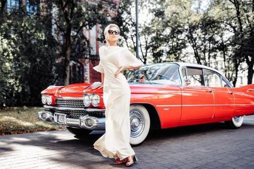 sieviete pie sarkanas automašīnas
