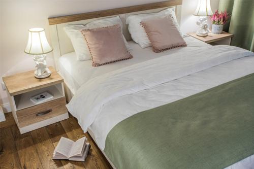 divguļamā gulda, kurai līdzās kāds ir nolicis grāmatu, lai var pakāpties un vieglāk iekāpt gultā