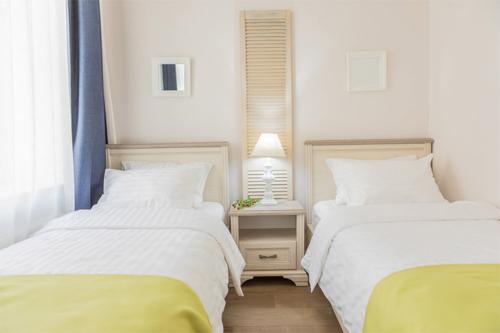 viesnīcas numuriņš ar divām atsevišķām gultām