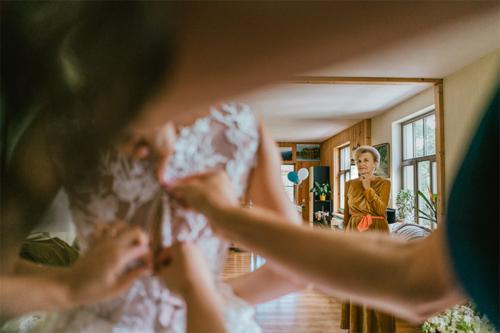 vecmamma vēro, kā mazmeitu ģērbj kāzām