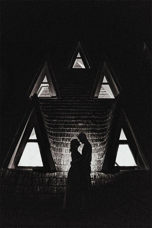 mākslinieciska jaunā pāra fotogrāfija tumšā telpā ar trīsstūrveida logiem