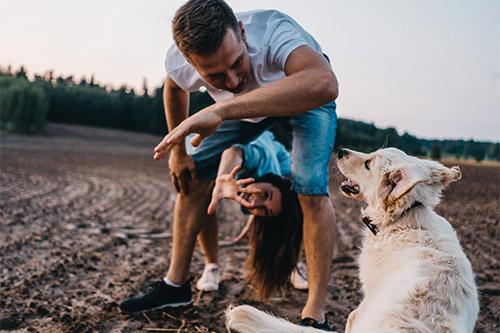 vīrietis, kuram starp kājām ir sieviete, un uz to visu noraugās viņu suns