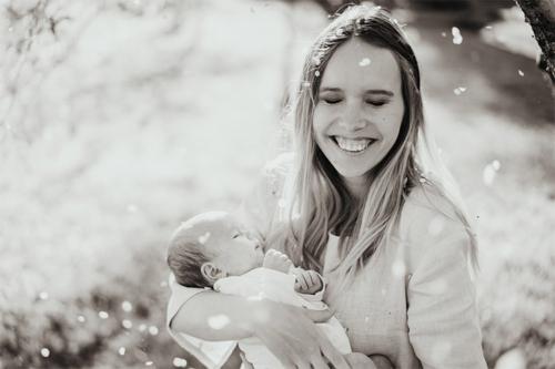 smaidīga sieviete ar mazuli rokās