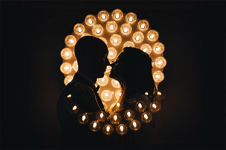 jaunā pāra skūpsts uz spuldzīšu fona tumsā