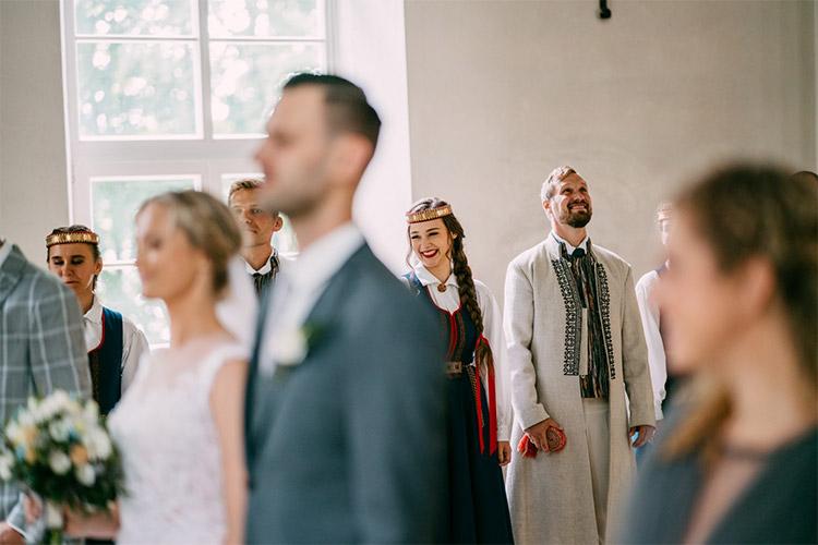 oriģinālas kāzas - fonā cilvēki tautiskos tērpos