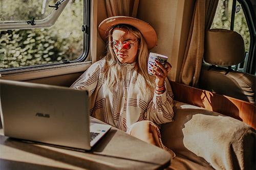 sieviete pie datora ar krūzi rokās