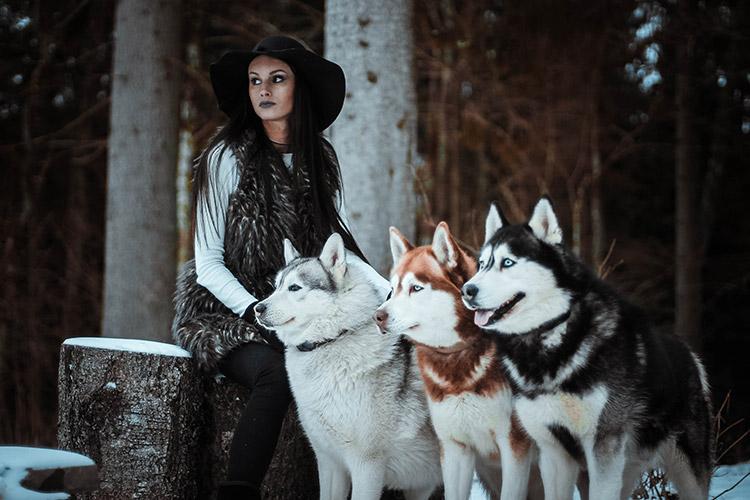sieviete kopā ar haskijiem mežā