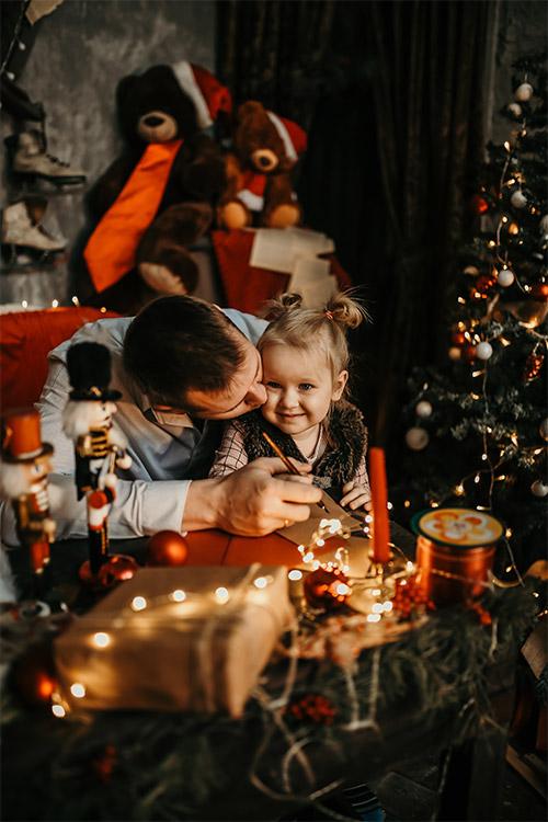 tēvs ar meitu pie Ziemassvētku eglītes